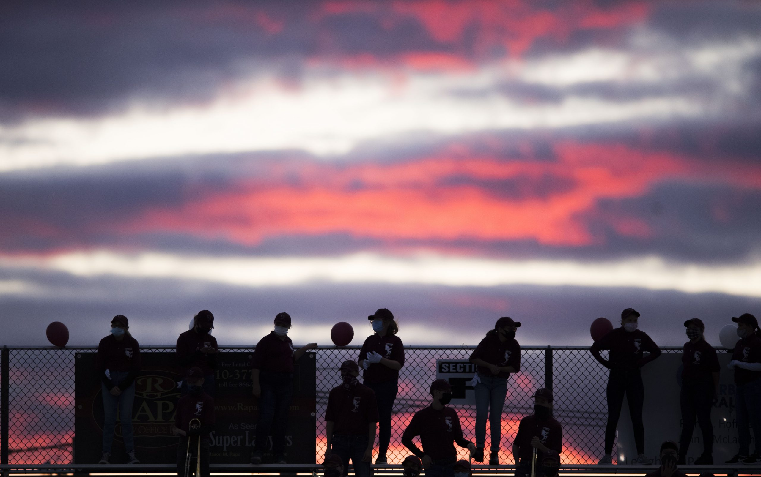 Fans stand atop the bleachers on a Friday evening at a recent home football game.